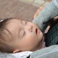 赤ちゃんが抱っこひもで寝ている画像