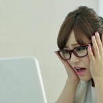 パソコンを見るメガネをかけた女性が困っている画像