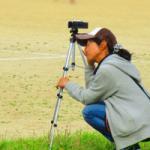 運動会でビデオを撮る帽子をかぶった女性の画像