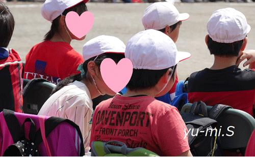 運動会で順番待ちをしている女の子と男の子の写真