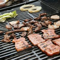 バーベキューでお肉と野菜を焼いている画像